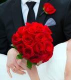 关闭新娘和新郎、花束和钮扣眼上插的花 免版税库存图片