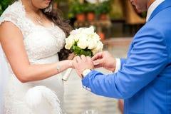 关闭新郎在新娘上把婚戒放 图库摄影