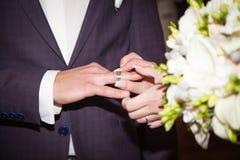 关闭新郎在新娘上把婚戒放 库存照片