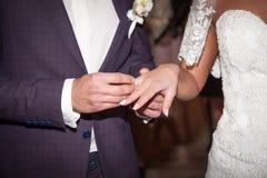 关闭新郎在新娘上把婚戒放 免版税库存图片