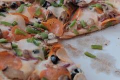 关闭新鲜的被烘烤的辣香肠烘饼 低贱比萨切片背景 热的比萨切片用在一土气木的熔化的乳酪 免版税库存图片