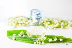 关闭新鲜的铃兰围拢的圆香水瓶、可以百合花和绿色叶子在白色backgroun 免版税库存照片