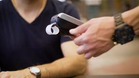 关闭无钱的付款在餐馆 给顾客POS终端和现金传票的侍者 蓝色人衬衣 股票录像