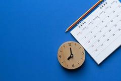 关闭日历、时钟和铅笔在蓝色背景 免版税库存图片
