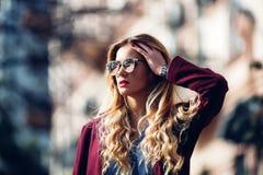 关闭时尚街道俏丽的女孩窗框画象秋天偶然成套装备美好白肤金发摆在的室外 免版税库存照片
