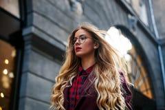 关闭时尚街道俏丽的女孩窗框画象秋天偶然成套装备美好白肤金发摆在的室外 图库摄影