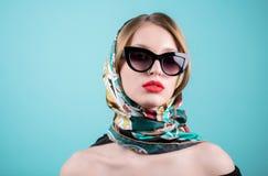 关闭时髦的少妇射击太阳镜的,并且您上色了披肩,头巾,反对蓝色背景的围巾 美好的fema 免版税图库摄影