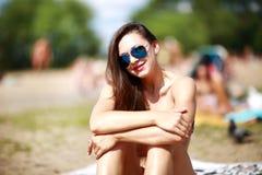 关闭时髦的美丽的性感的妇女画象玻璃的和有在一个晴朗的海滩的湿头发的与大海 免版税库存照片