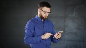 关闭时髦的镜片的英俊的有胡子的人,站立在办公室和运转使用智能手机的蓝色衬衣 股票录像
