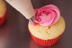 关闭是桃红色玫瑰结霜的杯形蛋糕用管道输送的水平的 免版税库存图片