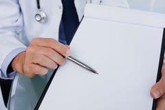 关闭显示一个空白文件的一位男性医生 免版税库存照片