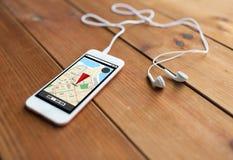 关闭智能手机和耳机在木头 库存图片