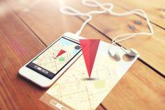 关闭智能手机和耳机在木头 免版税库存照片