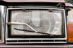 关闭有一个刮水器的一个车灯在老汽车 免版税库存图片