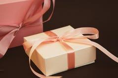 关闭有一把桃红色弓的礼物盒在布朗背景 礼物,生日 概念玻璃现有量扩大化的销售额 复制文本的空间 图库摄影