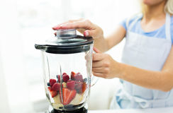 关闭有做水果饮料的搅拌器的妇女 免版税图库摄影