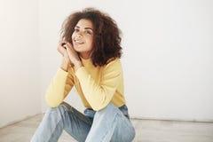 关闭有减速火箭的卷曲发型的年轻悦目快乐的非洲女孩在时髦的黄色高领衫和葡萄酒 免版税库存照片