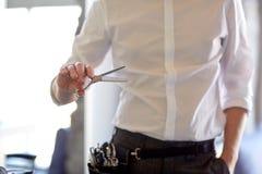 关闭有剪刀的男性美发师在沙龙 免版税库存图片