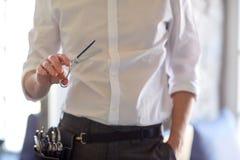 关闭有剪刀的男性美发师在沙龙 免版税图库摄影