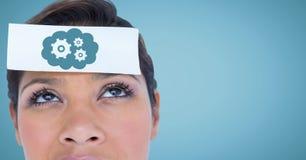 关闭有卡片的妇女在显示蓝色云彩和齿轮图表的头反对蓝色背景 免版税图库摄影
