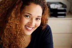 关闭有卷发微笑的可爱的年轻混合的族种妇女 免版税库存图片