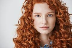 关闭有卷曲红色看在白色背景的头发和雀斑的美丽的女孩照相机 免版税库存图片
