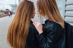关闭有吸引力的年轻夫妇耳语对耳朵秘密和微笑 愉快的关系概念 免版税图库摄影