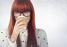 关闭有咖啡杯的妇女在面孔对白色墙壁 免版税库存图片