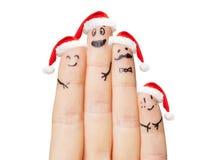 关闭有四个手指的手在圣诞老人帽子 库存图片