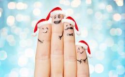 关闭有四个手指的手在圣诞老人帽子 免版税库存图片