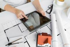 关闭有图纸和片剂个人计算机的手 免版税库存图片