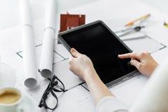 关闭有图纸和片剂个人计算机的手 图库摄影