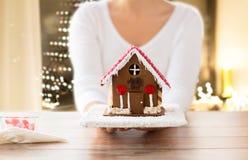 关闭有圣诞节华而不实的屋的妇女 免版税库存图片