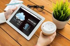 关闭有天气的妇女在片剂个人计算机熔铸了 免版税库存图片