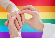 关闭有婚戒的女同性恋的夫妇手 免版税图库摄影