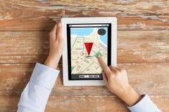 关闭有导航员地图的手在片剂个人计算机 免版税库存图片