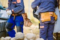 关闭有工具袋的两名建筑工人 库存图片