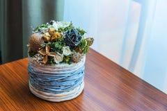 关闭有干花的布置的一个柳条花盆在一张木桌由窗口 库存照片