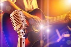 关闭有弹在带的音乐家的减速火箭的话筒声学吉他在夜音乐会 库存图片