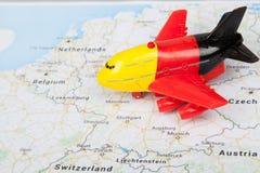 关闭有德国旗子的飞机玩具,登陆在欧洲地图 汽车城市概念都伯林映射小的旅行 图库摄影