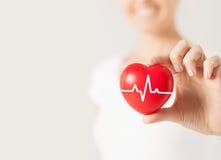 关闭有心电图的手在红色心脏 免版税库存照片
