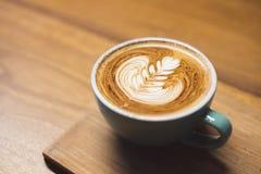 关闭有心脏形状拿铁艺术的热的热奶咖啡咖啡杯  库存图片