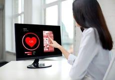 关闭有心脏脉冲的妇女在计算机上 免版税图库摄影