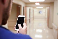 关闭有手机的护士在医院走廊 库存图片
