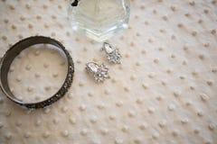 关闭有手镯和香水瓶的耳环在化装室 免版税库存图片