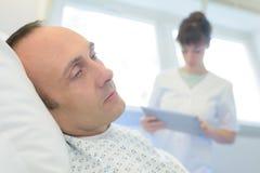 关闭有护士的男性患者 图库摄影