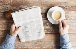 关闭有报纸和咖啡的男性手 免版税库存图片