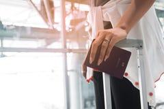 关闭有拿着护照和手提箱,旅行概念的定婚戒指的妇女手 库存图片
