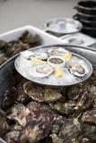关闭有新鲜的被去外皮的牡蛎盘子的服务器与担当开胃菜柠檬的 免版税库存图片