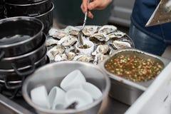 关闭有新鲜的被去外皮的牡蛎盘子的服务器与担当开胃菜柠檬的 库存图片